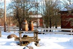 Oude melkblikken op landbouwbedrijf in Zweden Stock Fotografie