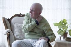 Oude mens die aan pijn lijden stock foto