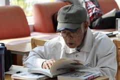 Oude mens die in bibliotheek bestuderen Stock Foto