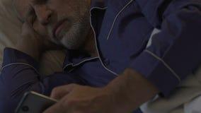 Oude mens die in bed wakker bij nacht liggen die mobiele telefoon, problemen met slaap scrollen stock video