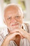 Oude mens die bij camera glimlacht stock foto