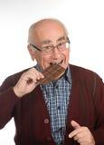 Oude mens die chocolade eten stock afbeelding