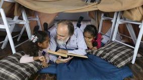 Oude mens die de Bijbel met kleinkinderen lezen stock videobeelden