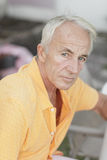 Oude mens die de camera bekijkt Stock Foto's