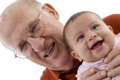 Oude mens die de leuke baby houdt stock foto's