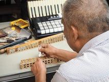Oude mens die de rietblokken van een harmonika herstellen, stock foto