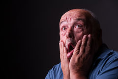 Oude mens die doen schrikken of gek kijken stock foto