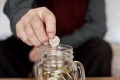 Oude mens die een één euro muntstuk in een glaspot opslaan Royalty-vrije Stock Afbeeldingen