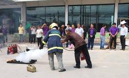 Oude mens die een brandoefening uitoefenen die een brand met een poedertype brandblusapparaat doven Stock Foto