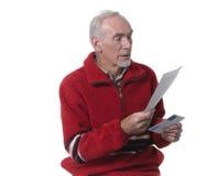 Oude mens die een brief leest Stock Foto
