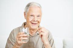 Oude mens die een pil slikken Royalty-vrije Stock Afbeelding