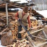 Oude mens die het brandhout zagen stock foto's