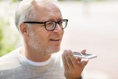 Oude mens die het registreertoestel van het stembevel op smartphone met behulp van Royalty-vrije Stock Foto's