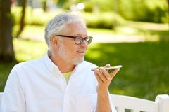 Oude mens die het registreertoestel van het stembevel op smartphone met behulp van Stock Fotografie