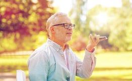 Oude mens die het registreertoestel van het stembevel op smartphone met behulp van Royalty-vrije Stock Afbeeldingen