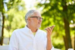 Oude mens die het registreertoestel van het stembevel op smartphone met behulp van Stock Afbeeldingen