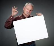 Oude mens die leeg aanplakbord houdt Stock Afbeelding