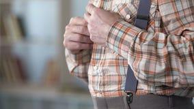 Oude mens die met bevende handen omhoog overhemd, het beginnen dichtknopen van de ziekte van Alzheimer stock videobeelden