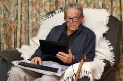 Oude mens die met laptop computer thuis werken Royalty-vrije Stock Afbeeldingen