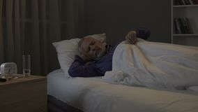 Oude mens die nachtmerries in zijn dromen zien, die in afdeling van verpleeghuis slapen stock footage