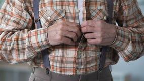 Oude mens die omhoog overhemd dichtknopen, die aan trilling, Alzheimer, seniele ziekten lijden stock footage