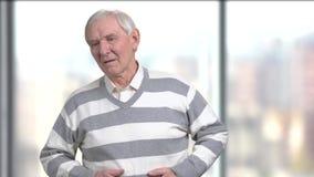 Oude mens die ongemak in buik hebben stock video