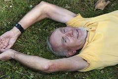 Oude mens die op het gras ligt Royalty-vrije Stock Foto