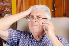 Oude mens die op telefoon spreekt Stock Afbeelding