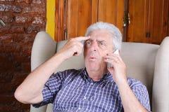Oude mens die op telefoon spreekt Stock Foto