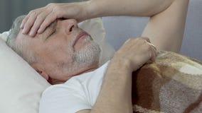 Oude mens die in slapeloos bed liggen, houdend hand tegen voorhoofd, slechte hoofdpijn stock video