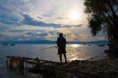 Oude mens die tijdens zonsondergang vissen royalty-vrije stock afbeeldingen