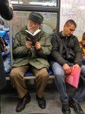 Oude mens die in twee glazen een boekzitting in een trein lezen Stock Foto