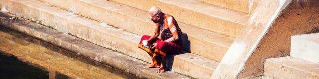 Oude mens die typische robe dragen die bij de Tempelpool van Sree Padmanabhaswamy tijdens de zonnige dag in Trivandrum, India sit Royalty-vrije Stock Foto