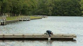 Oude mens die voor visserij op de pijler voorbereidingen treffen stock video
