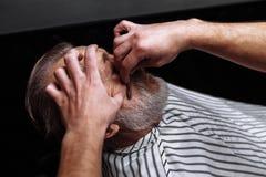 Oude mens die zijn die baard krijgen door kapper wordt geschoren stock foto's
