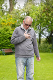 Oude mens die zijn borst houden Stock Afbeeldingen