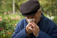 Oude mens die zijn neus blaast stock afbeelding