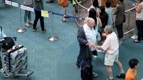 Oude mens die zijn vriend koesteren bij internationale aankomsthal stock video