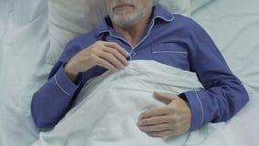 Oude mens die zoet in bed slapen, die zich op overkant omkeren, die van comfort genieten stock video