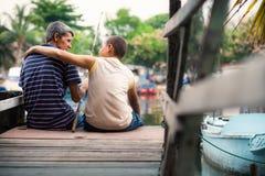 Oude mens en jongen die samen op rivier voor pret vissen Royalty-vrije Stock Afbeeldingen