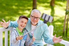 Oude mens en jongen die selfie door smartphone nemen Royalty-vrije Stock Afbeelding