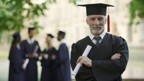 Oude mens in graduatieuitrusting, professor die nieuwe graad, academische carrière verkrijgen stock videobeelden