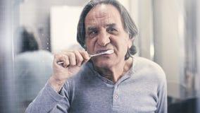 Oude mens het borstelen tanden voor de spiegel stock foto's