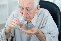 Oude mens het drinken pillen Stock Foto's