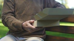 Oude mens het openen kartondoos en het kijken foto, voorbij geheugen, nostalgie, archief stock videobeelden