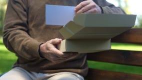 Oude mens het openen kartondoos en het kijken foto, voorbij geheugen, nostalgie, archief royalty-vrije stock afbeeldingen