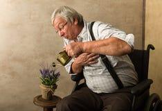 Oude mens het water geven installatie Stock Foto