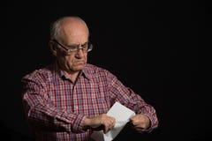 Oude mens met bankdocument stock foto's