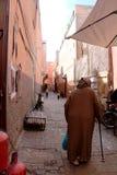 Oude mens met een het lopen riet in traditionele djeallabah in een straat van Marrakech stock foto