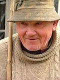 Oude mens met een hoed en een wandelstok stock foto